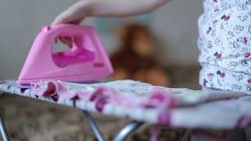 La bambina sta rivestendo di ferro i vestiti archivi video