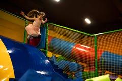La bambina sta saltando nello stagno asciutto con i cubi molli luminosi per gioco in bambini gioca la stanza fotografia stock