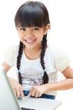 La bambina sta sedendosi con il suo computer portatile Fotografie Stock