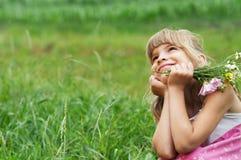 La bambina sta sedendosi nel prato Immagine Stock