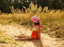 La bambina sta sedendosi sopra introduce il giorno soleggiato Fotografie Stock Libere da Diritti
