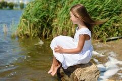 La bambina sta sedendosi su una roccia in vestito bianco il giorno soleggiato fotografia stock