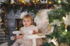 La bambina sta sedendosi su una sedia dall'albero di Natale nell'interno del ` s del nuovo anno immagine stock libera da diritti