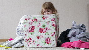 La bambina sta sedendosi in una scatola colorata gioca con i vestiti archivi video
