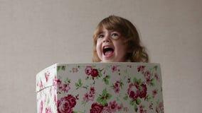 La bambina sta sedendosi in una scatola colorata guarda dalla scatola e sorride stock footage