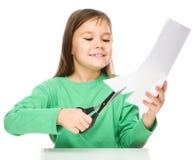 La bambina sta tagliando la carta facendo uso delle forbici Fotografia Stock Libera da Diritti