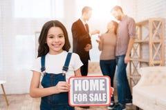 La bambina sta tenendo il segno con l'iscrizione Camera da vendere L'agente immobiliare mostra l'appartamento alle coppie fotografia stock
