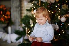 La bambina sta tenendo un giocattolo e sorridere dell'albero di Natale fotografia stock libera da diritti