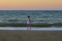 La bambina sta in una posa vaga e negli sguardi al tramonto fotografia stock libera da diritti