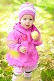 La bambina su un glade con una mela Immagine Stock
