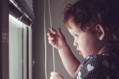 La bambina sui ciechi di finestra si apre Immagine Stock Libera da Diritti