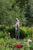 La bambina sulle spalle di papà chiude i suoi occhi con le sue mani Immagine Stock