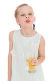 La bambina sveglia beve il succo d'arancia fotografie stock
