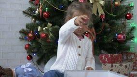 La bambina sveglia che gioca con il contenitore e la ghirlanda di regalo vicino ha decorato l'albero di Natale video d archivio