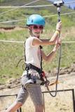 La bambina sveglia che scala sull'corde all'aperto scorre Immagine Stock