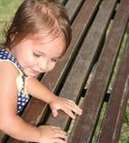 La bambina sveglia che si arrampica in cima ad una sosta di legno è fotografia stock