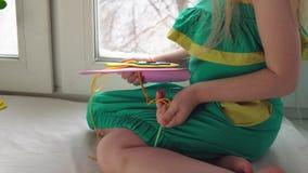 La bambina sveglia cuce una borsa rosa stock footage