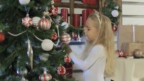La bambina sveglia decora l'albero di Natale stock footage