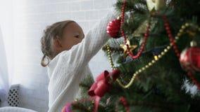 La bambina sveglia decora l'albero di Natale video d archivio