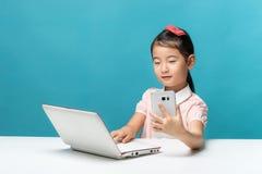 La bambina sveglia dell'Asia sta sedendosi alla tavola con il suo computer portatile bianco Immagini Stock Libere da Diritti