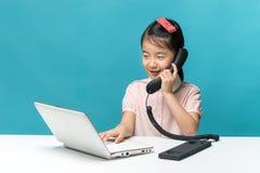 La bambina sveglia dell'Asia sta sedendosi alla tavola con il suo computer portatile bianco Fotografia Stock Libera da Diritti