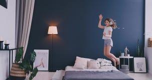 La bambina sveglia divertente in cuffie senza fili che ballano il canto con il pettine e si diverte nella mattina di festa che sa archivi video
