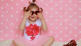 La bambina sveglia divertente si agghinda e prova sopra i vetri soleggiati, i sorrisi e le risate Bambino felice video d archivio