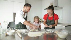 La bambina sveglia ed i suoi bei genitori stanno cucinando Hanno insieme molto divertimento e sorridendo in cucina a casa archivi video