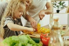 La bambina sveglia ed i suoi bei genitori stanno tagliando le verdure in cucina a casa fotografia stock libera da diritti