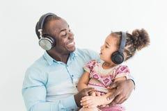 La bambina sveglia ed il suo papà stanno ascoltando musica con le cuffie su un fondo bianco immagini stock libere da diritti