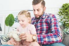 La bambina sveglia ed suo padre stanno giocando al dottore a casa immagini stock