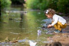 La bambina sveglia esegue una barca di carta nella corrente Immagine Stock Libera da Diritti