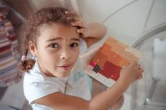 La bambina sveglia fa l'applique, incolla la casa variopinta, applicante una carta di colore facendo uso del bastone della colla  fotografia stock libera da diritti