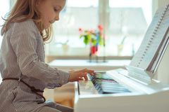 La bambina sveglia ha addestramento con il piano Immagine Stock