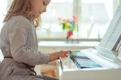 La bambina sveglia ha addestramento con il piano Fotografia Stock