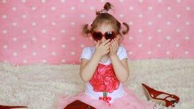 La bambina sveglia in occhiali da sole rossi sotto forma dei cuori invia i baci dell'aria Fondo rosa Fashionista video d archivio