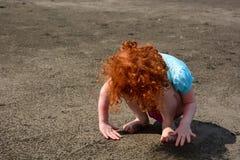 La bambina sveglia paga con la sabbia sulla spiaggia di Bali Fotografie Stock