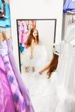 La bambina sveglia prova sopra il vestito che guarda in specchio Immagine Stock