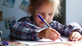 La bambina sveglia si siede alla sua Tabella e disegna con i pastelli stock footage