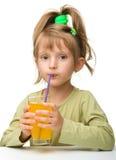 La bambina sveglia sta bevendo il succo di arancia Immagini Stock Libere da Diritti
