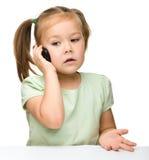 La bambina sveglia sta comunicando su un telefono delle cellule Immagini Stock