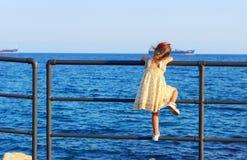 La bambina sveglia sta esaminando il sole si tuffa l'ampio mare Fotografia Stock Libera da Diritti
