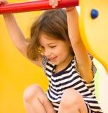 La bambina sveglia sta giocando in campo da giuoco Immagini Stock Libere da Diritti