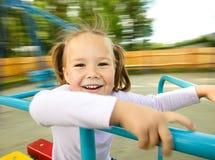 La bambina sveglia sta guidando sul merry-go-round Immagine Stock