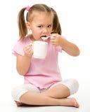 La bambina sveglia sta mangiando il yogurt Fotografie Stock Libere da Diritti