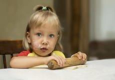 La bambina sveglia sta rotolando la pasta con il perno di legno Fotografia Stock