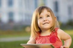 La bambina sveglia sta sedendosi con una compressa sull'erba nel parco Ritratto impressionabile Formazione iniziale Fotografie Stock
