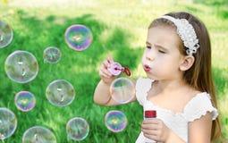 La bambina sveglia sta soffiando le bolle di sapone Fotografie Stock