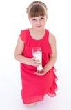 La bambina sveglia sta tenendo il grande bicchiere di latte immagini stock libere da diritti