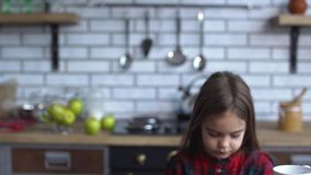 La bambina sveglia in una camicia a quadretti che prende una tazza e si siede al tavolo da cucina stock footage